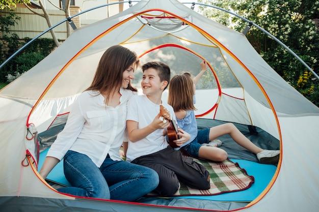 テントの中でウクレレをしながら彼の母親を見ている少年