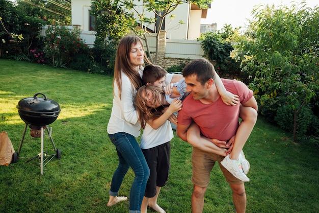 公園で屋外ピクニックを楽しんで幸せな家族
