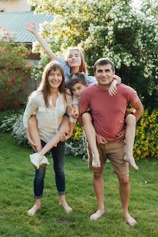 公園で背中に子供たちを運ぶ美しい親