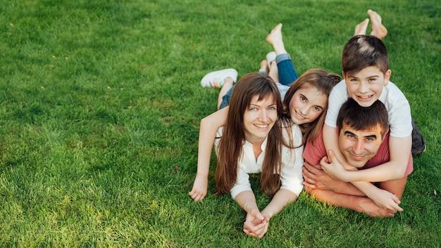 Родители и их двое прекрасных детей, лежа на траве в парке