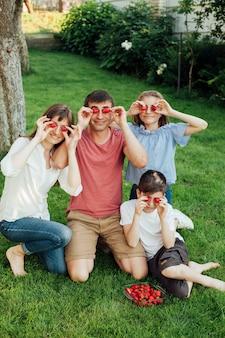 ピクニック中に新鮮なイチゴと彼らの目を覆っている笑顔の家族