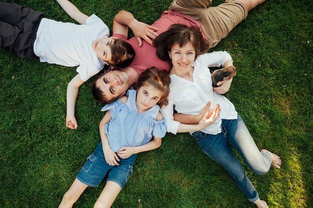 幸せな親と子供たちは公園で芝生の上に横たわる