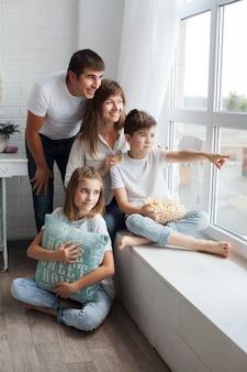 窓から両親と姉に何かを見せている少年