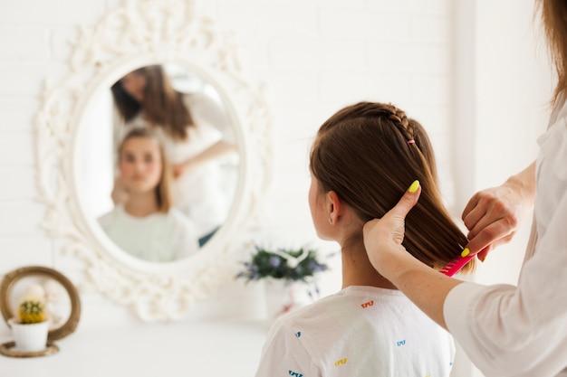 彼女の娘の髪を自宅で結ぶ母の背面図