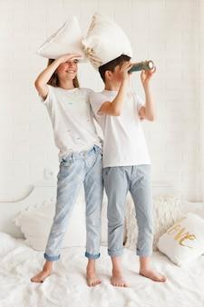 望遠鏡を通して見る彼女の兄弟と一緒にベッドの上に立っている目のシールド女の子