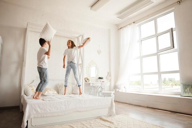 Братья и сестры вместе с подушкой воюют на кровати в спальне