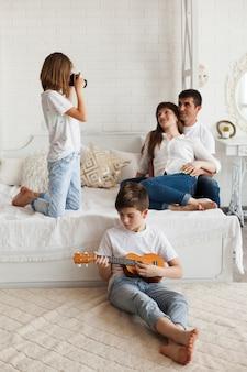 両親の写真を撮る彼の妹の前でウクレレを弾いている少年