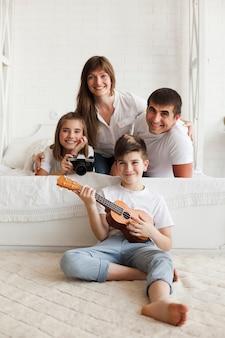 Улыбающийся родитель со своими детьми, глядя на камеру