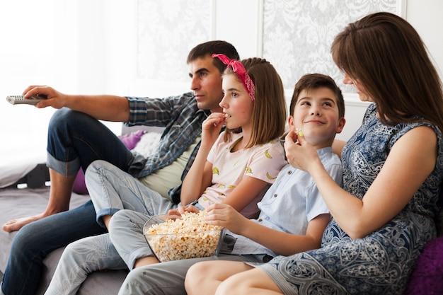 家でテレビを見ながらポップコーンを食べる家族