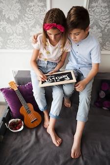 自宅でスレートに家族のテキストを書く彼の妹と一緒に立地の少年