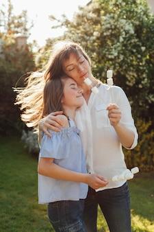 Мать и дочь держат шашлык из зефира с закрытыми глазами в парке