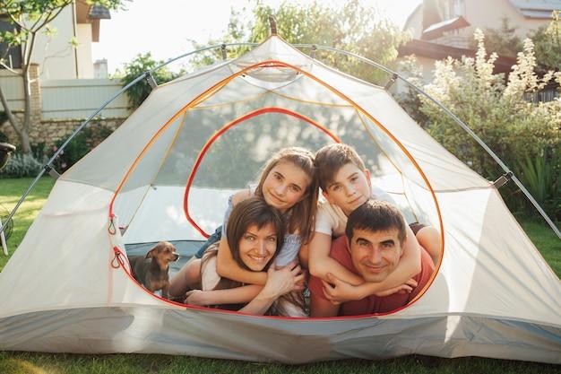 テントの中で彼らの子供と一緒に休日のピクニックを楽しんでいる笑顔の親