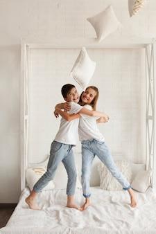 Счастливый брат и сестра обнимаются на кровати у себя дома