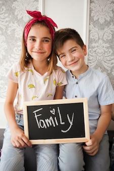 弟と妹がカメラ目線の家族のテキストとスレートを保持