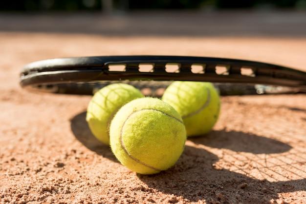 Теннисные мячи и черная ракетка