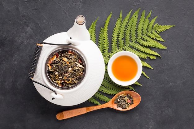 Сухие листья травы и листья папоротника с травяным чаем на черной поверхности