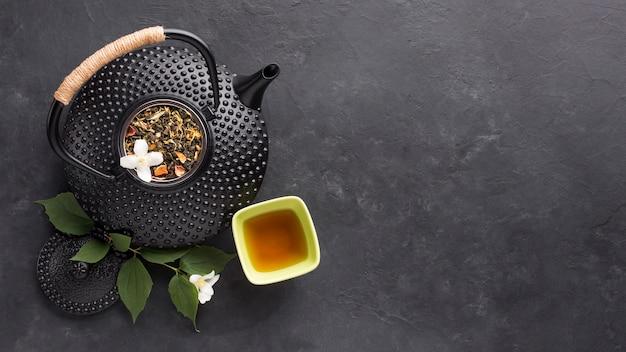Вид сверху травяной чай со свежим белым цветком жасмина на черном фоне