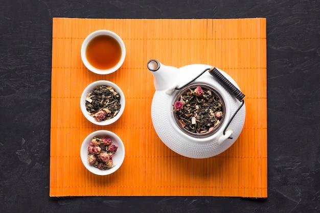 Травяной чай и его ингредиенты, расположенные в ряд с чайником на оранжевом коврике на черном фоне