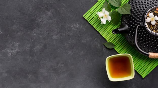 Повышенный вид травяного чая и его ингредиента на черной текстурированной поверхности