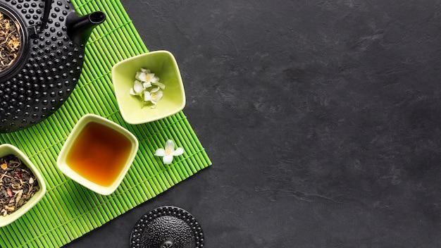 Сухая чайная трава и травяной чай с белым цветком жасмина на зеленом столовом приборе на черном фоне