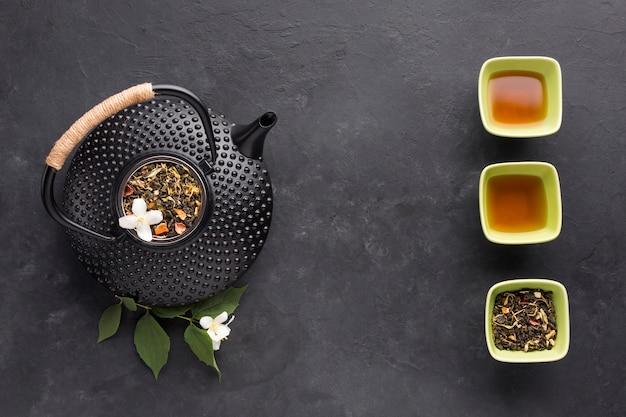 乾燥茶成分と織り目加工の黒いティーポットの立面図