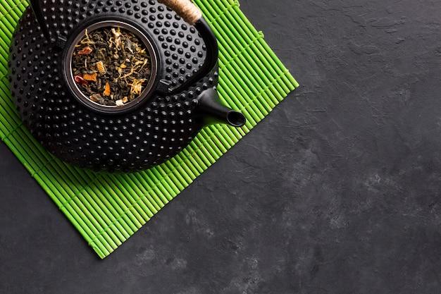 Повышенный вид черного чайника с травой высушенного чая на зеленом столовом приборе