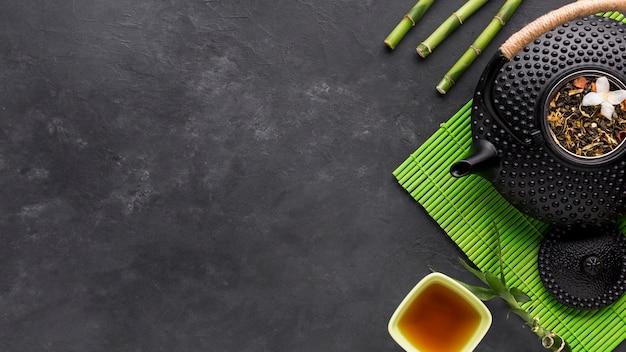 Вид сверху сушеной травы и бамбуковой палочки с чайником на черном фоне