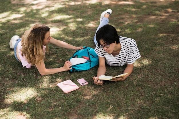 Вскользь студенты подростка на зеленом луге в парке