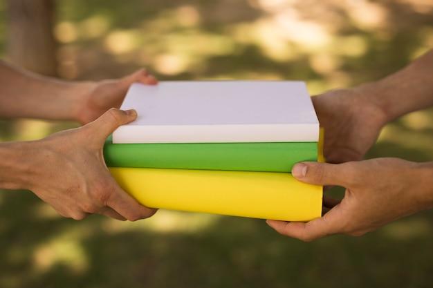 作物の学生が公園で教科書の山を渡す