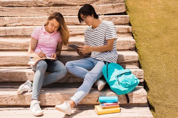 Подростки вместе делают домашнее задание на лестнице
