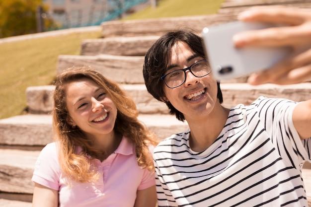 カメラに笑顔多民族のかわいいカップル