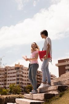 Молодые подростковые пары на лестнице против городского пейзажа