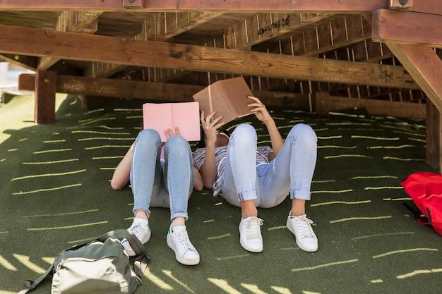 カジュアルな学生が芝生の上で本を読む