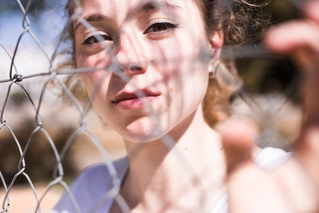 Молодая красивая девушка, глядя через металлическую сетку