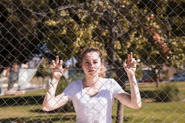 Молодая девушка держится за металлическую сетку