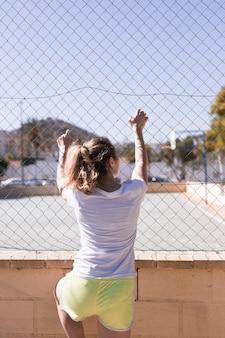 Молодая спортивная девушка держит на металлический забор