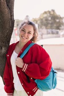 バックパックと木の近くに立っている若い女の子