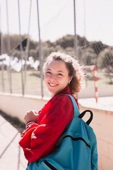 スポーツグラウンドの近くの若い微笑の女の子