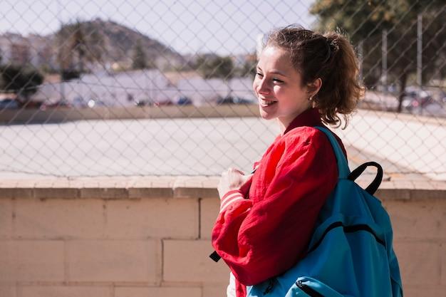 スポーツグラウンドの近くに立っている若いきれいな女の子
