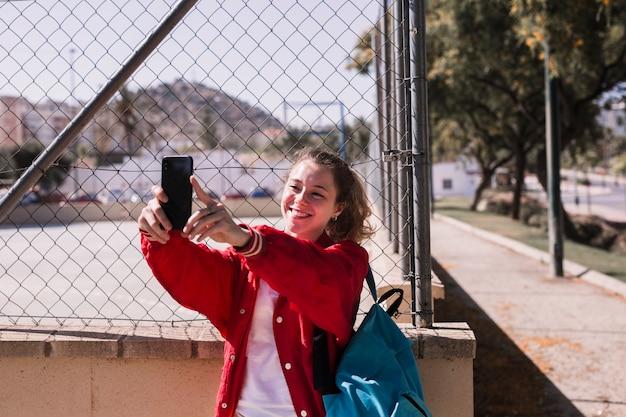 若い女の子がスポーツグラウンド近くのスマートフォンで写真を撮る
