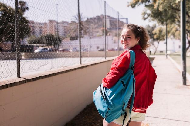 スポーツグラウンドの近くを歩く若い女の子