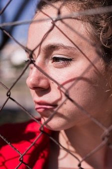 Лицо молодой задумчивой девушки за металлической сеткой