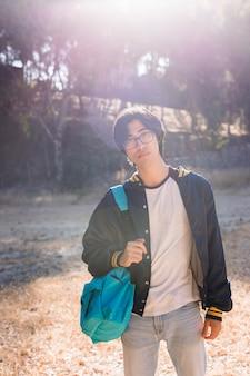 Молодой азиатский подросток стоя в парке