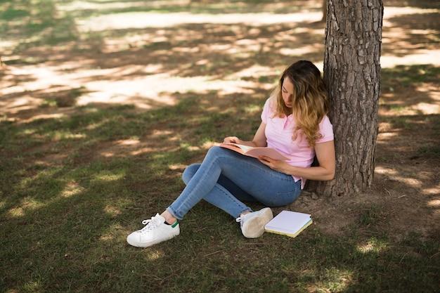 Молодая женщина учится в парке