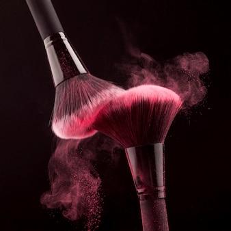 渦巻くピンクの粉と化粧筆