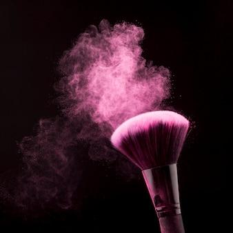粉と黒の背景に化粧用ブラシの明るいほこり
