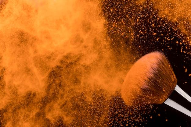 Заморозить движение частиц оранжевого сухого порошка и кисти