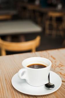 机の上のステンレス鋼のスプーンでエスプレッソコーヒーのカップ