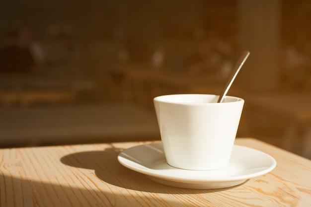 コーヒーカップとソーサーの木製の机の上の影