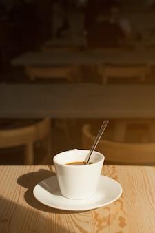 Вкусная чашка кофе с блюдцем на столе в кафе